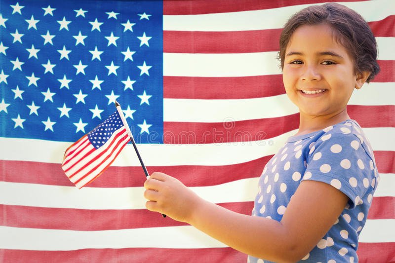 Composite image of cute girl with american flag. Cute girl with american flag against rippled us flag stock photography