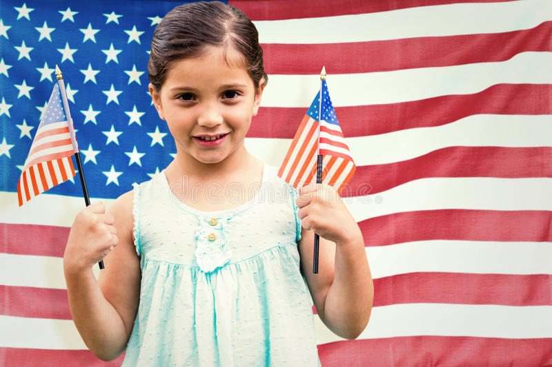 Composite image of cute girl with american flag. Cute girl with american flag against rippled us flag stock photo
