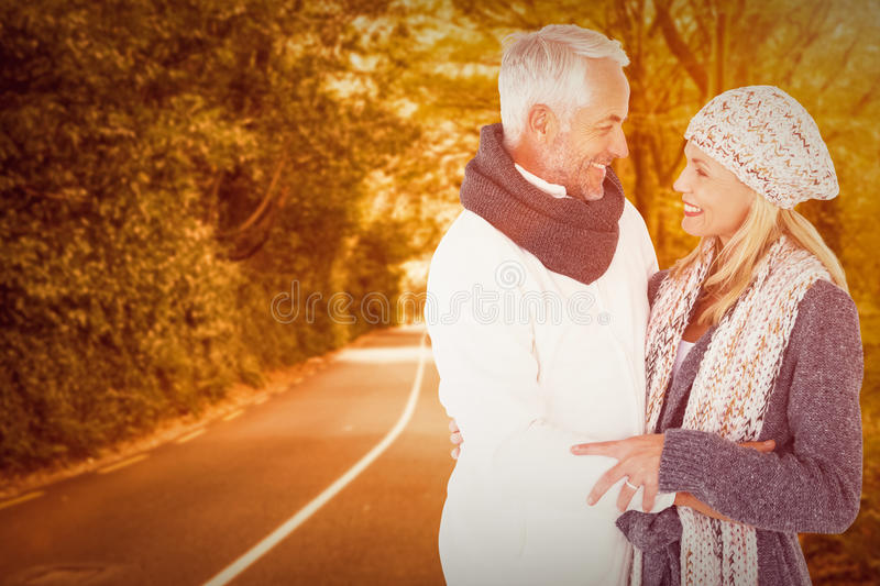 Composite image of cute happy couple romancing. Cute happy couple romancing against country road stock photo