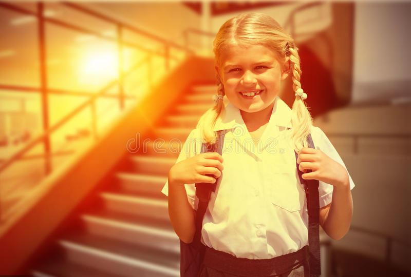 Composite image of cute pupil smiling at camera by the school bus. Cute pupil smiling at camera by the school bus against empty stair way royalty free stock images