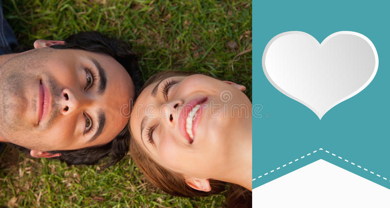 Composite image of cute valentines couple. Close up of two friends looking at each other while lying head to head against heart label royalty free illustration