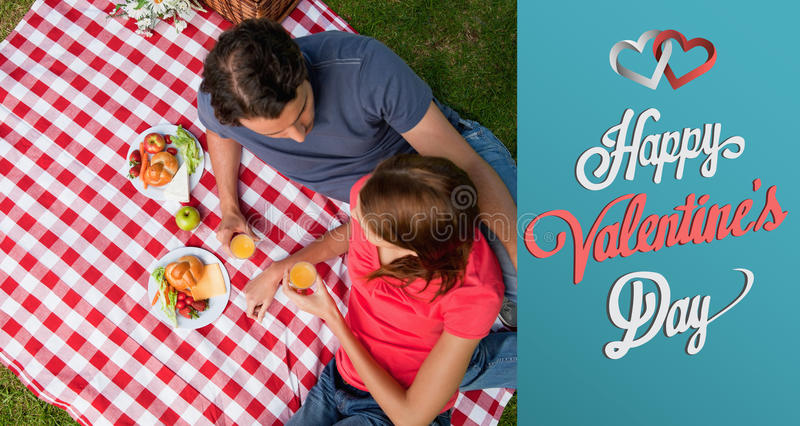 Composite image of cute valentines couple. Elevated view of two friends lying on a blanket with a picnic against cute valentines message stock illustration