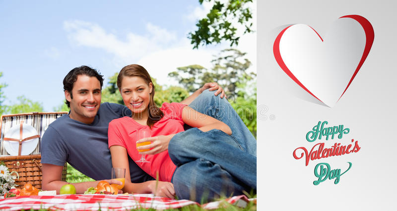 Composite image of cute valentines couple. Two friends looking ahead while they hold glasses as they lie on a blanket against cute valentines message stock illustration