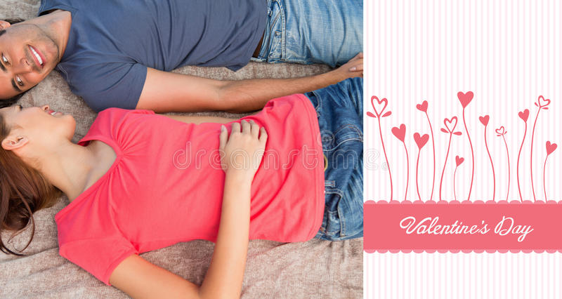 Composite image of cute valentines couple. Two friends looking at each other while lying on a quilt against valentines graphic royalty free illustration