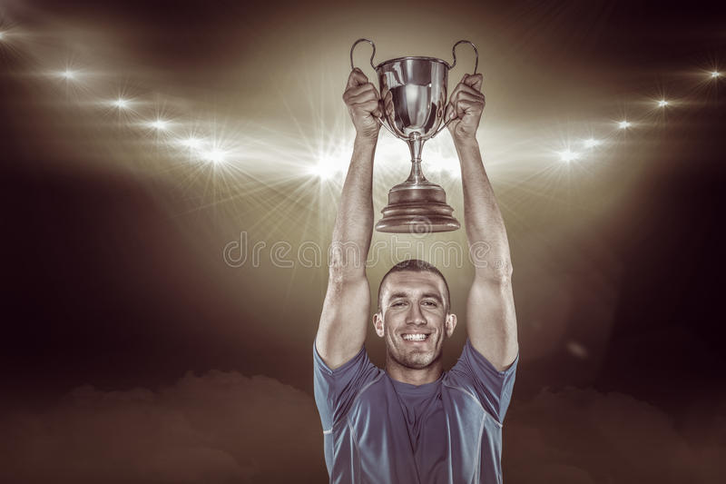 Composite image 3D of portrait of smiling rugby player holding trophy stock photos