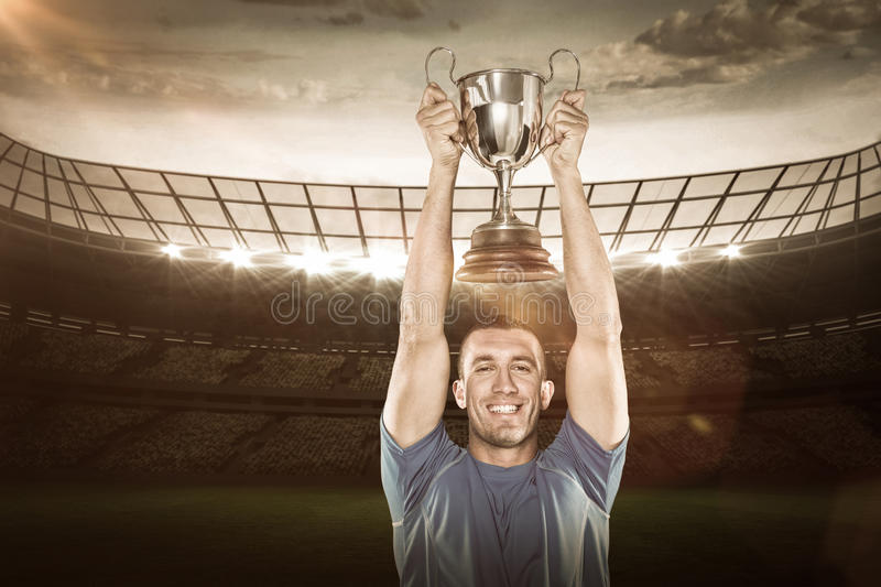 Composite image 3D of portrait of smiling rugby player holding trophy stock image