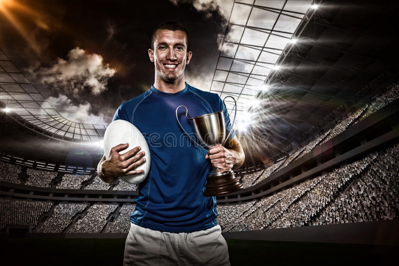 Composite image 3D of portrait of smiling rugby player holding trophy and ball royalty free stock photography