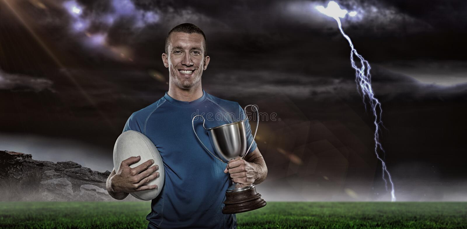 Composite image 3D of portrait of smiling rugby player holding trophy and ball stock image