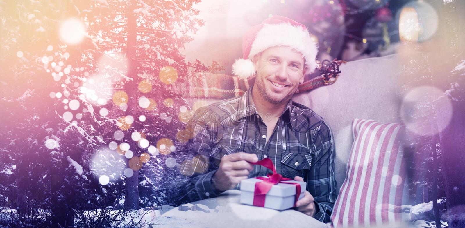 Composite image of defocused lights against snow covered trees and mountain. Defocused lights against snow covered trees and mountain against happy man in santa royalty free stock images