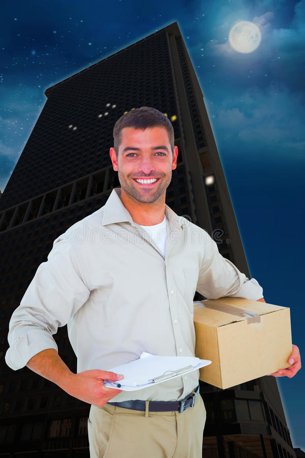 Composite image of delivery man with cardboard box and clipboard on white background royalty free stock photos