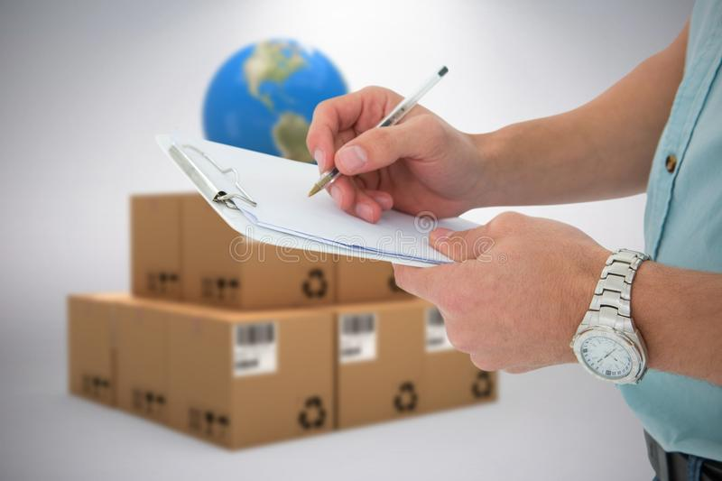 Composite image of delivery man writing on clipboard stock photo