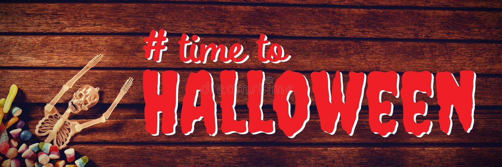 Composite image of digital composite image of time to halloween text. Digital composite image of time to Halloween text against skeleton decoration with candies stock image