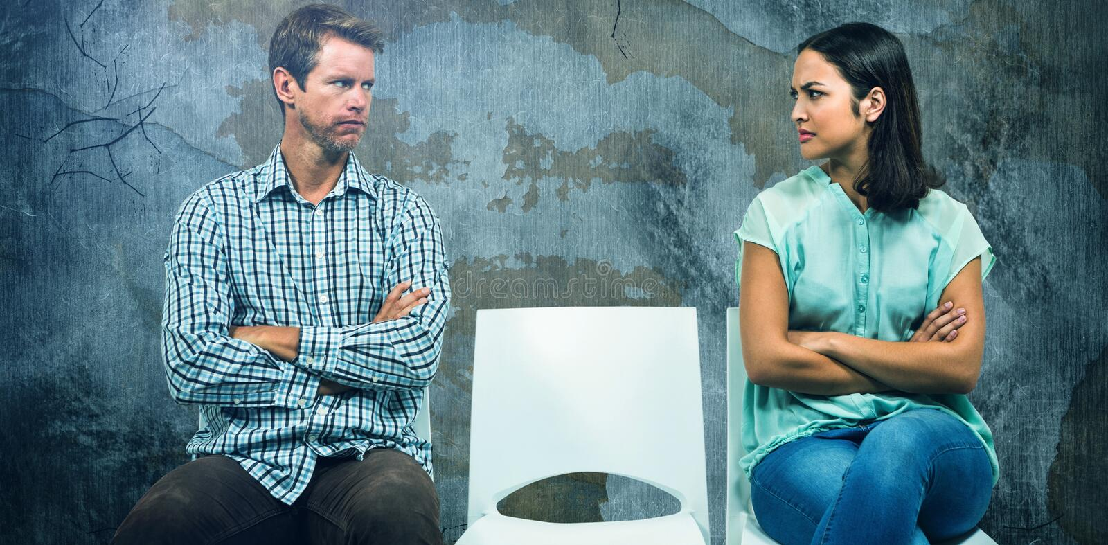 Composite image of displeased couple looking at each other while sitting on chairs stock photos
