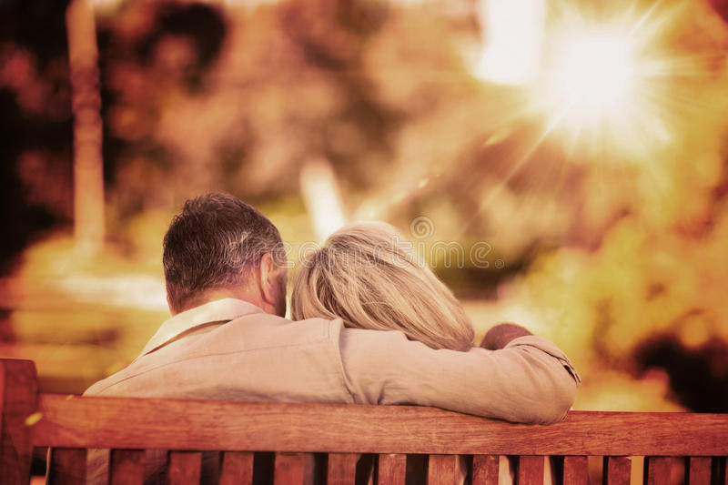 Composite image of elderly couple sitting on the bench with their back to the camera royalty free stock photography