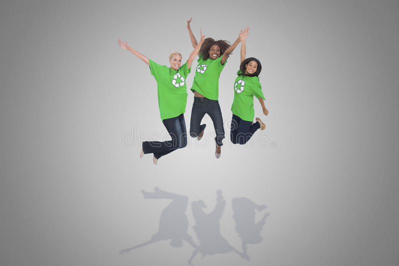 Composite image of enviromental activists jumping and smiling. Against grey vignette royalty free stock images