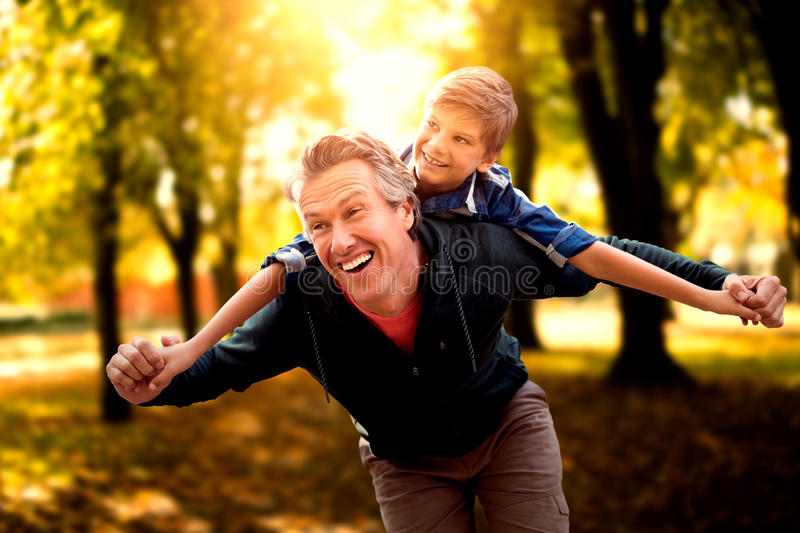 Composite image of father giving his son piggyback ride royalty free stock images