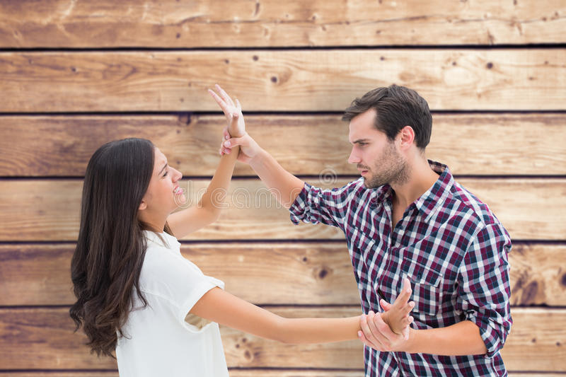 Composite image of fearful brunette being overpowered by boyfriend stock photo