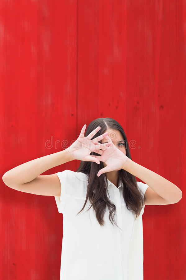 Composite image of fearful brunette covering her face stock photo