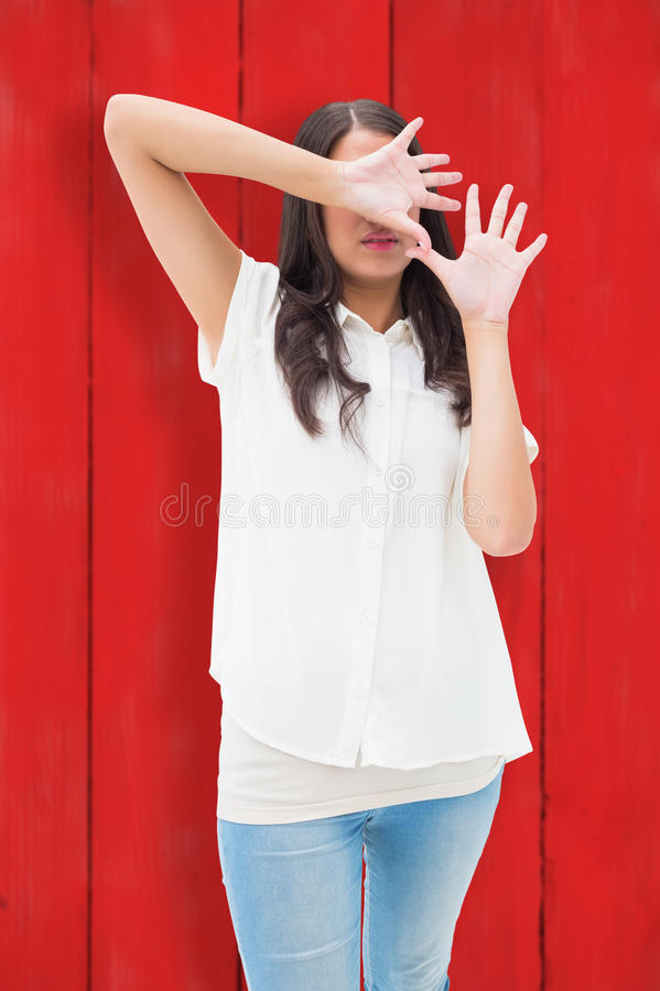 Composite image of fearful brunette covering her face stock images