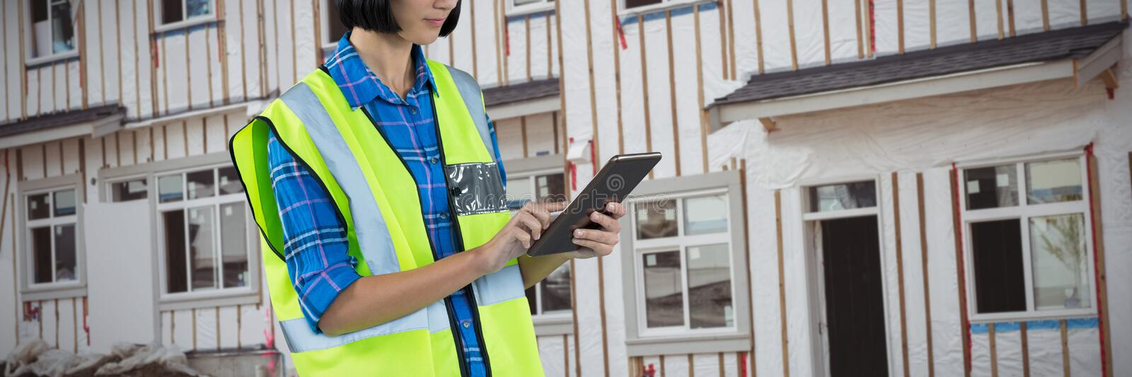 Composite image of female architect using digital tablet stock photography