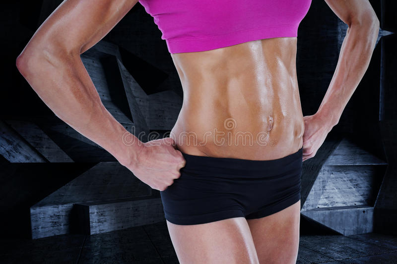 Composite image of female bodybuilder posing with hands on hips mid section stock illustration