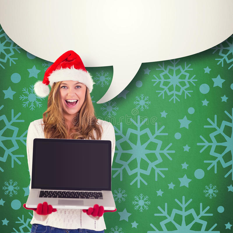 Composite image of festive blonde showing a laptop. Festive blonde showing a laptop against green vignette royalty free stock images