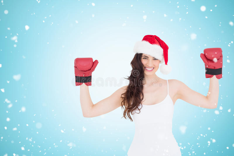 Composite image of festive brunette in boxing gloves with arms raised stock photography