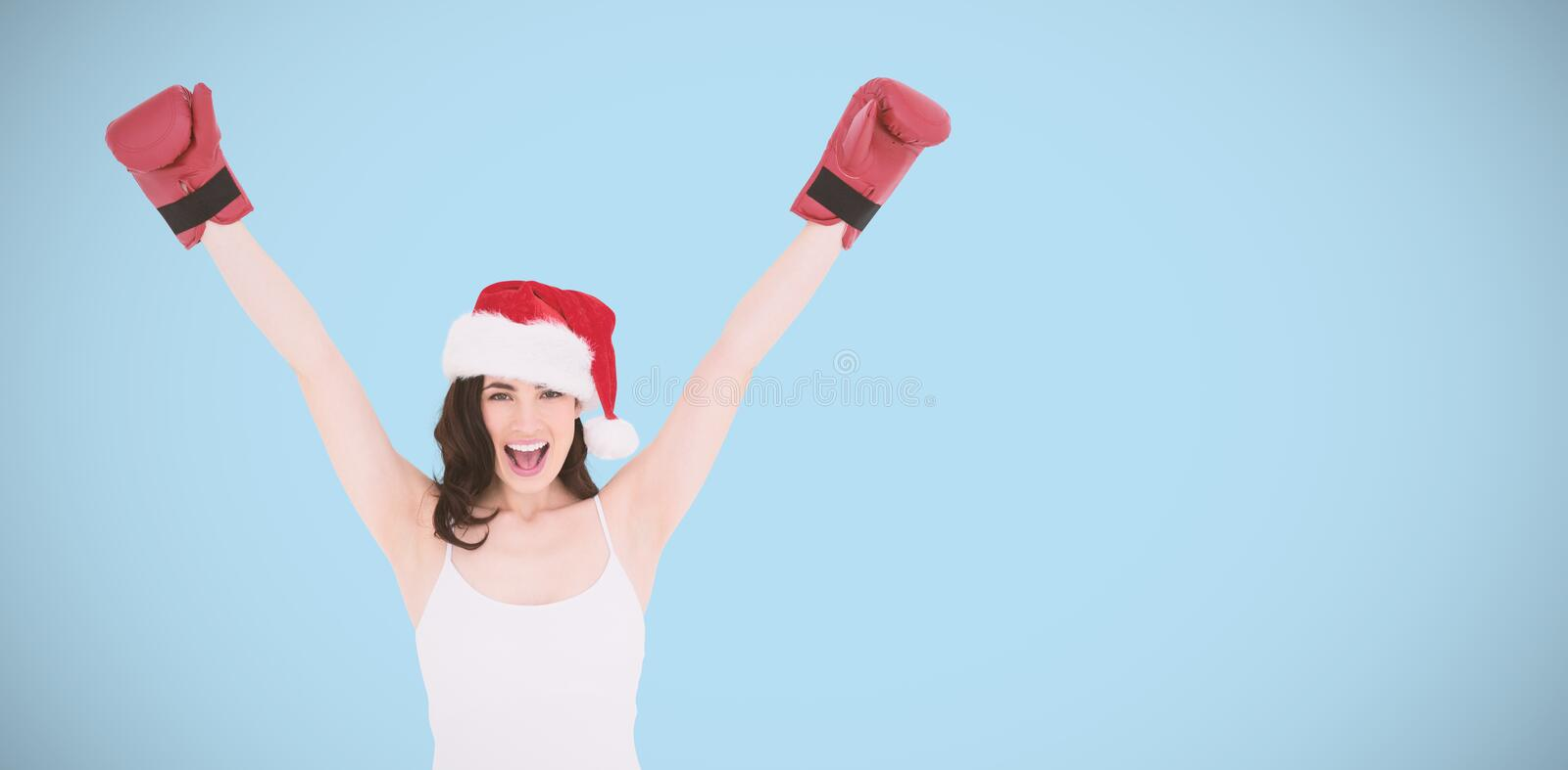 Composite image of festive brunette in boxing gloves cheering royalty free stock photo