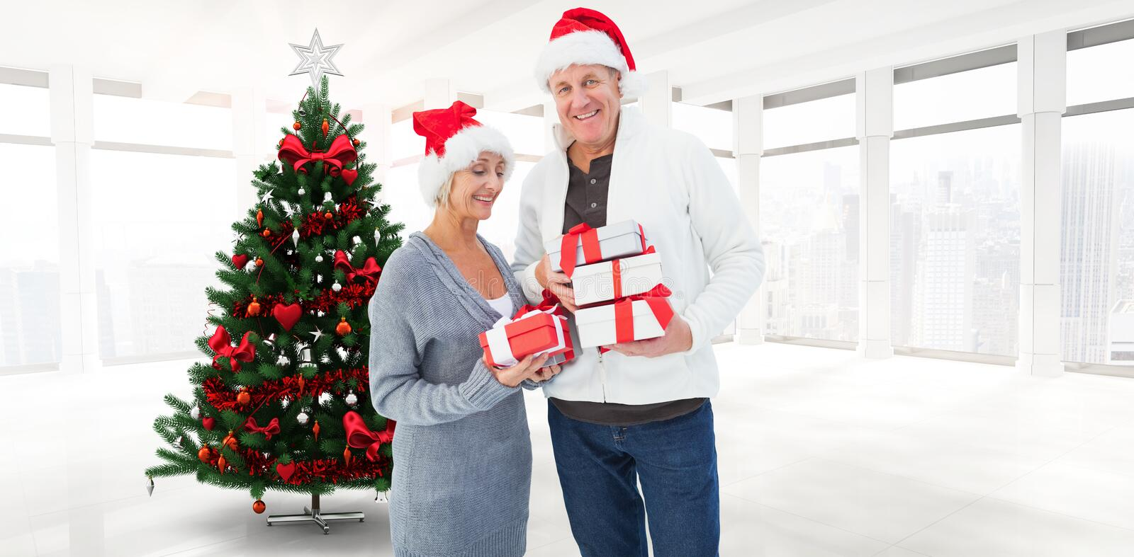 Composite image of festive mature couple holding christmas gifts stock images