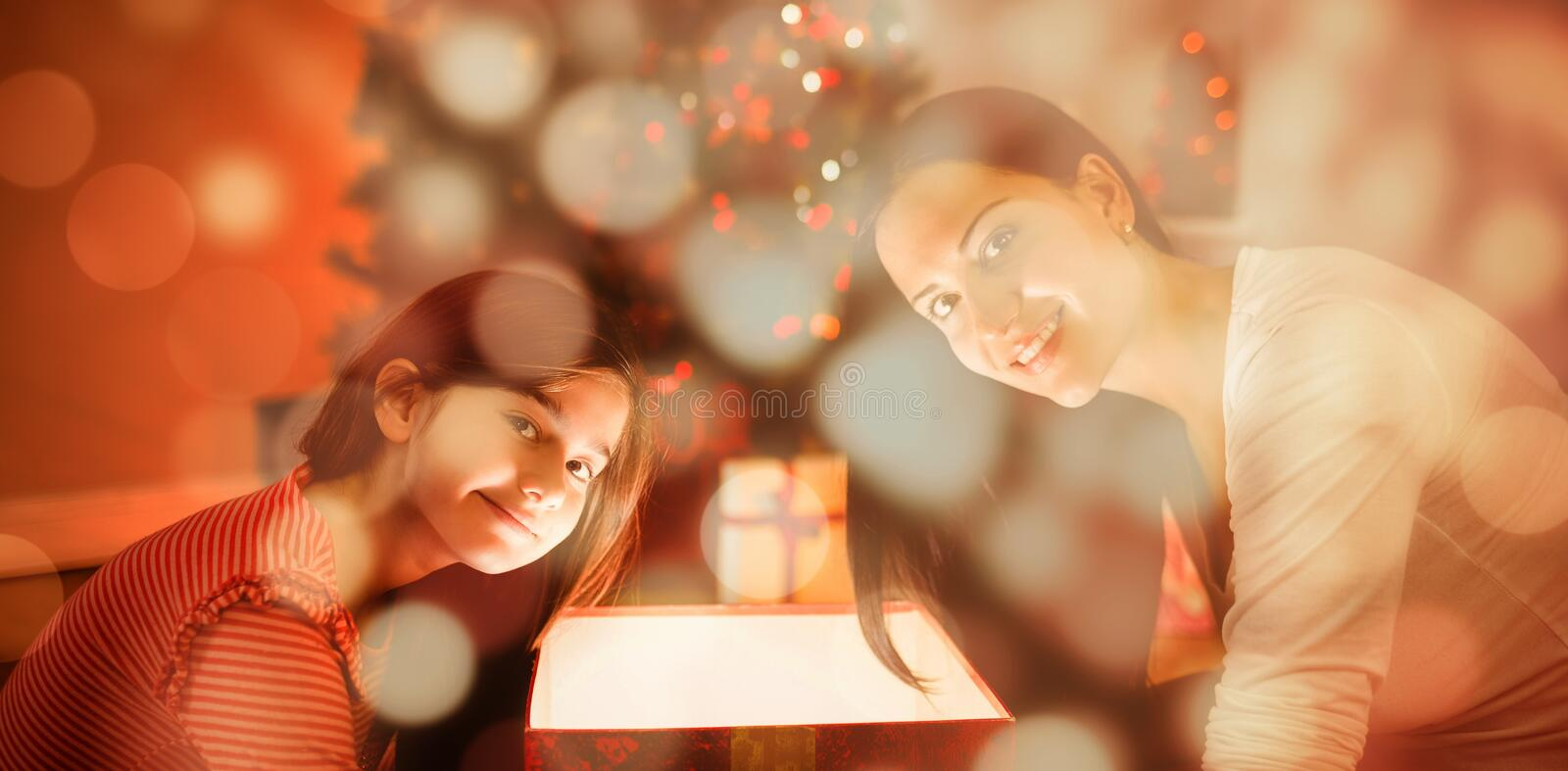 Composite image of festive mother and daughter opening a glowing christmas gift royalty free stock image