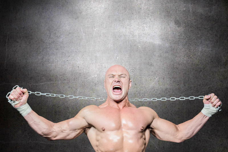 Composite image of fighter holding chain with arms raised stock photography