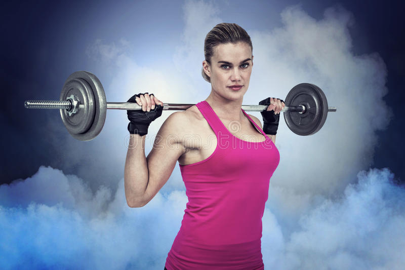 Composite image of fit woman with barbell royalty free stock image
