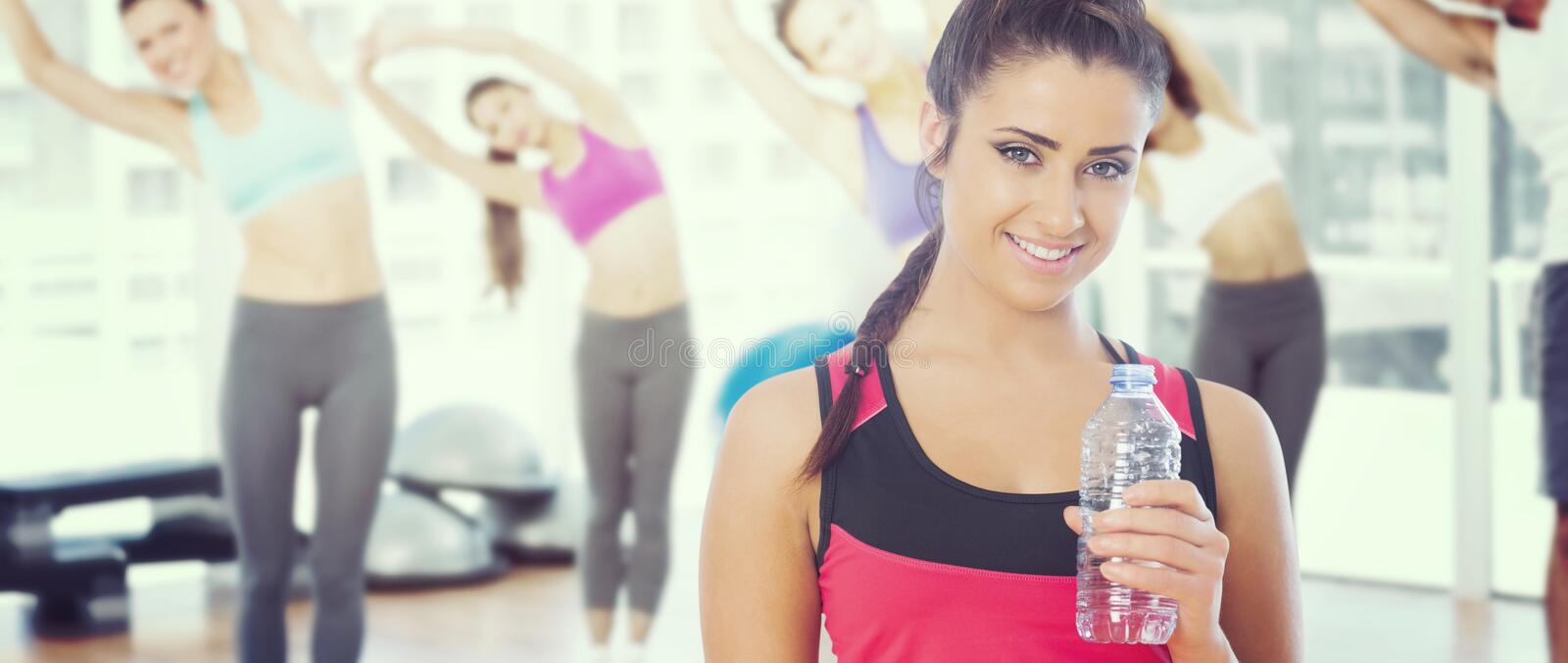 Composite image of fit woman holding water bottle stock image