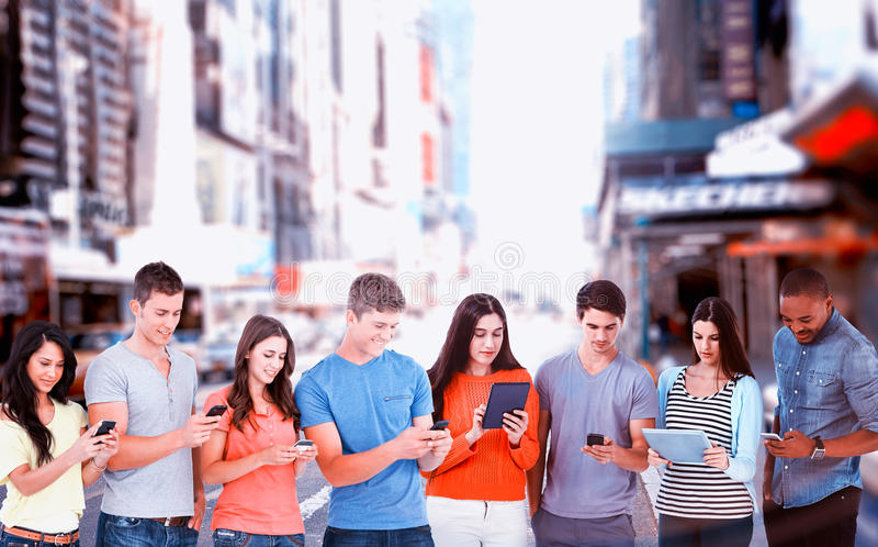 Composite image of four friends standing to the side slightly sending texts royalty free stock photography