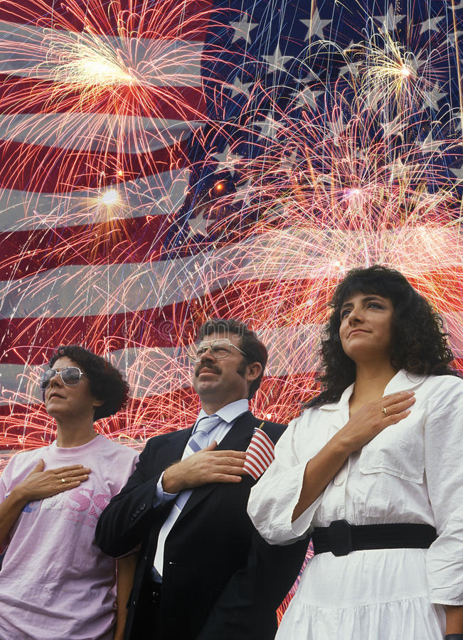 Composite image of four people at a citizenship ceremony superimposed over the American flag and fireworks royalty free stock photography