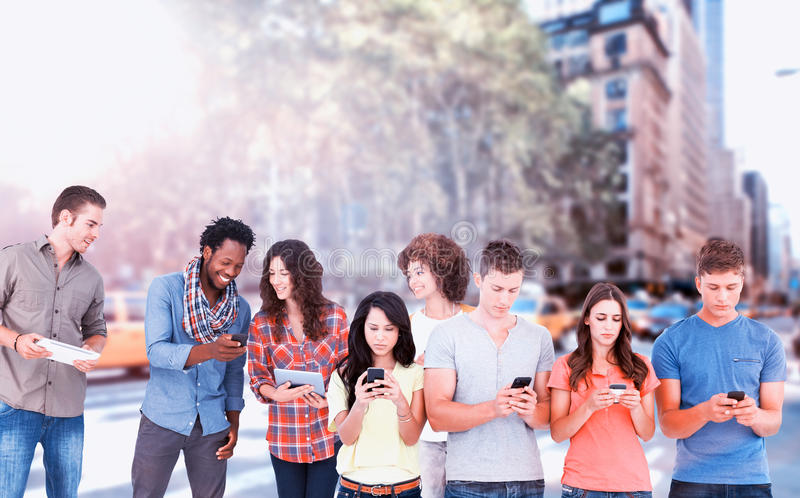 Composite image of four people standing beside each other and texting on their phones royalty free stock image