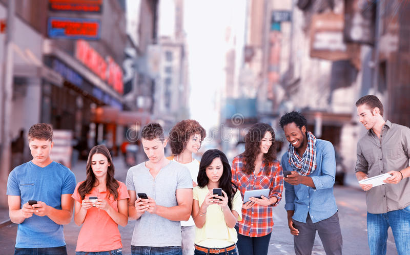 Composite image of four people standing beside each other and texting on their phones stock photo