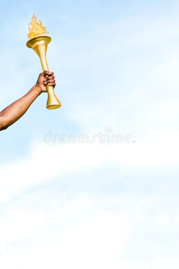 Composite image of front view of sportsman holding a cup. Front view of sportsman holding a cup against blue sky with clouds royalty free stock photo