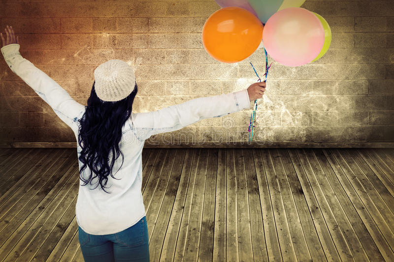 Composite image of full length rear view of carefree woman holding colorful balloons. Full length rear view of carefree woman holding colorful balloons against stock images