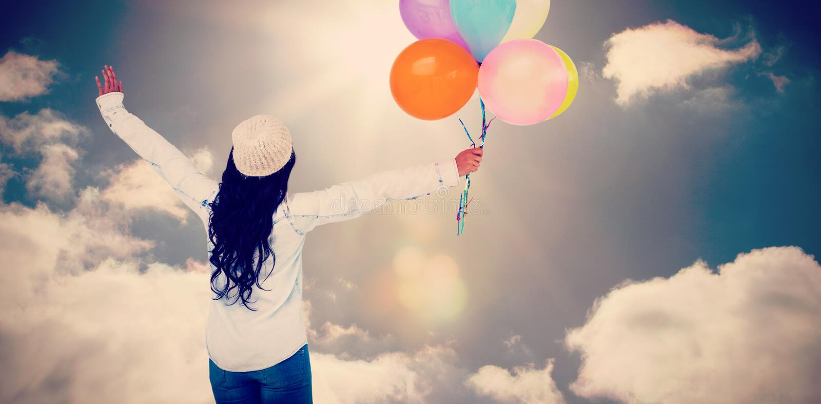 Composite image of full length rear view of carefree woman holding colorful balloons. Full length rear view of carefree woman holding colorful balloons against royalty free stock image