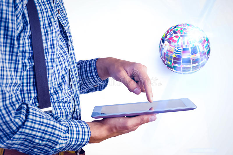 Composite image of geeky businessman using his tablet pc. Geeky businessman using his tablet pc against sphere made of flags royalty free stock photos
