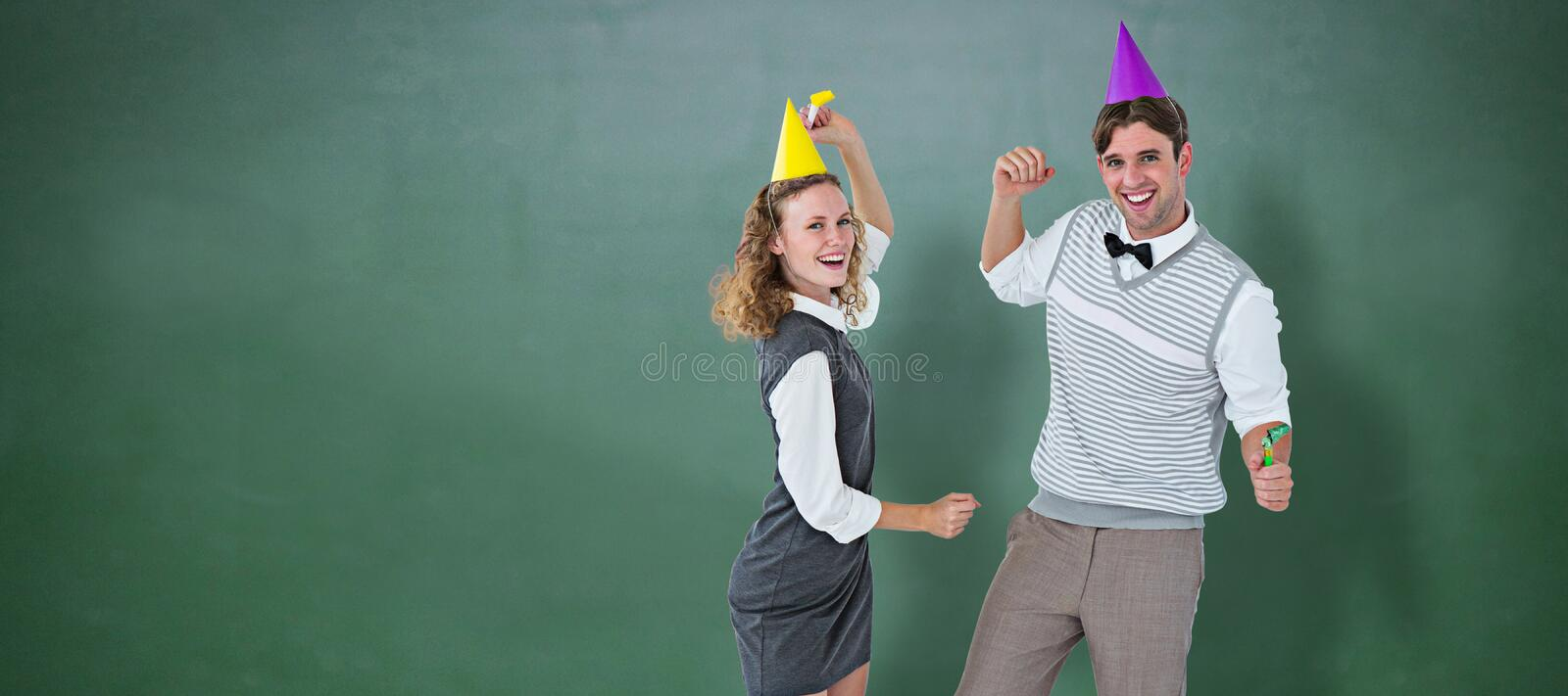 Composite image of geeky couple dancing with party hat. Geeky couple dancing with party hat against green chalkboard stock images