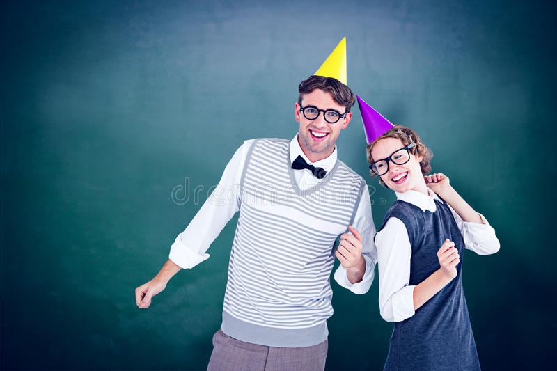 Composite image of geeky hipster couple wearing a party hat. Geeky hipster couple wearing a party hat against green chalkboard royalty free stock image