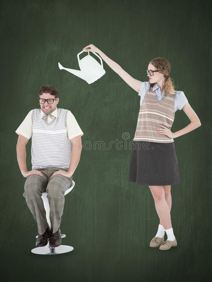 A Composite image of geeky hipster holding watering can above her boyfriend. Geeky hipster holding watering can above her boyfriend against green chalkboard royalty free stock photo