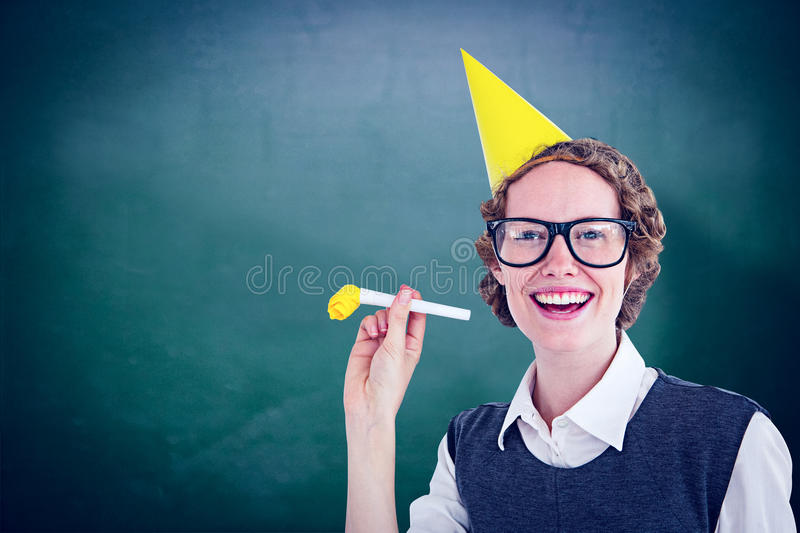 Composite image of geeky hipster in party hat with horn. Geeky hipster in party hat with horn against green chalkboard stock image