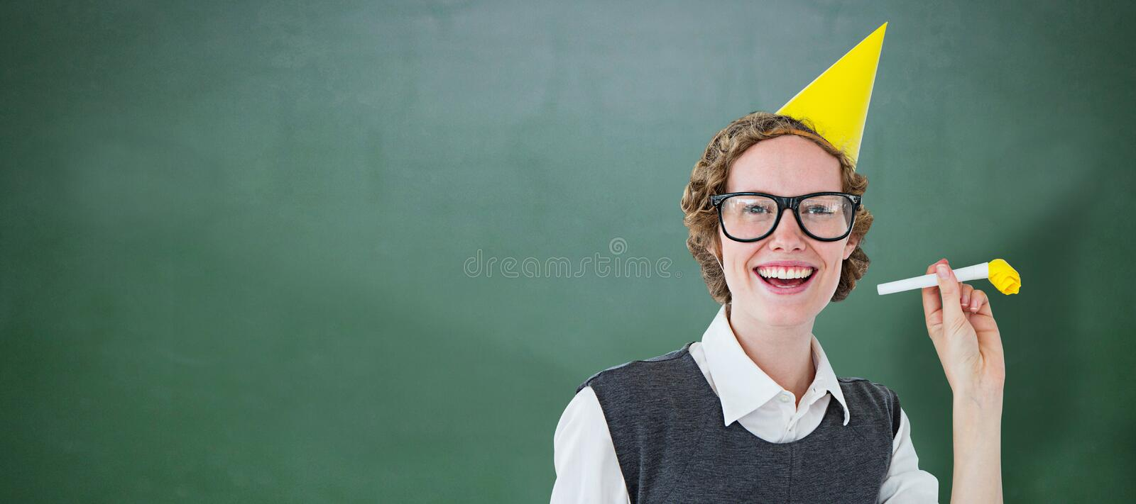 Composite image of geeky hipster in party hat with horn. Geeky hipster in party hat with horn against green chalkboard royalty free stock image