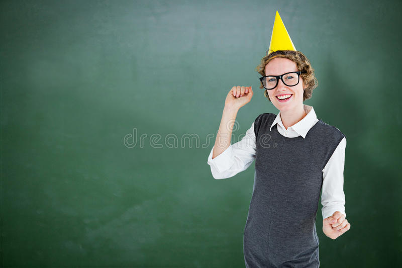 Composite image of geeky hipster wearing a party hat. Geeky hipster wearing a party hat against green chalkboard royalty free stock image