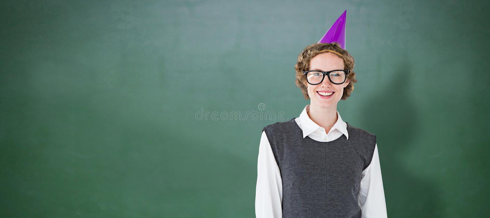 Composite image of geeky hipster wearing a party hat. Geeky hipster wearing a party hat against green chalkboard royalty free stock images