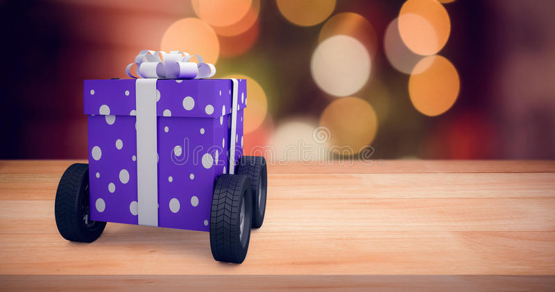 Composite image of gift box with gray ribbon on wheels. Gift box with gray ribbon on wheels against composite image of fake snow against illuminated background royalty free illustration