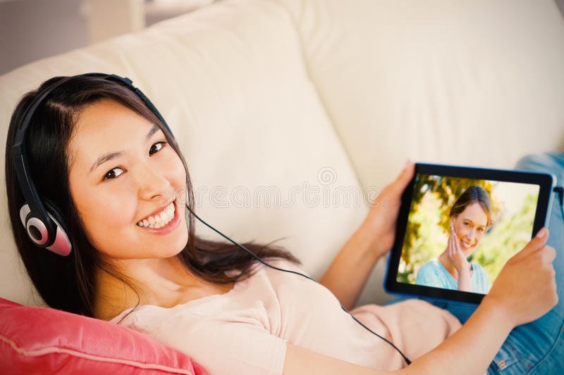 Composite image of girl using her tablet pc on the sofa and listening to music smiling at camera royalty free stock photo